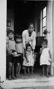 1934220px-COLLECTIE_TROPENMUSEUM_Portret_van_een_baboe_met_kinderen_in_de_deuropening_van_een_huis_voor_Europeanen_op_Aek_na_Oeli_TMnr_60051111